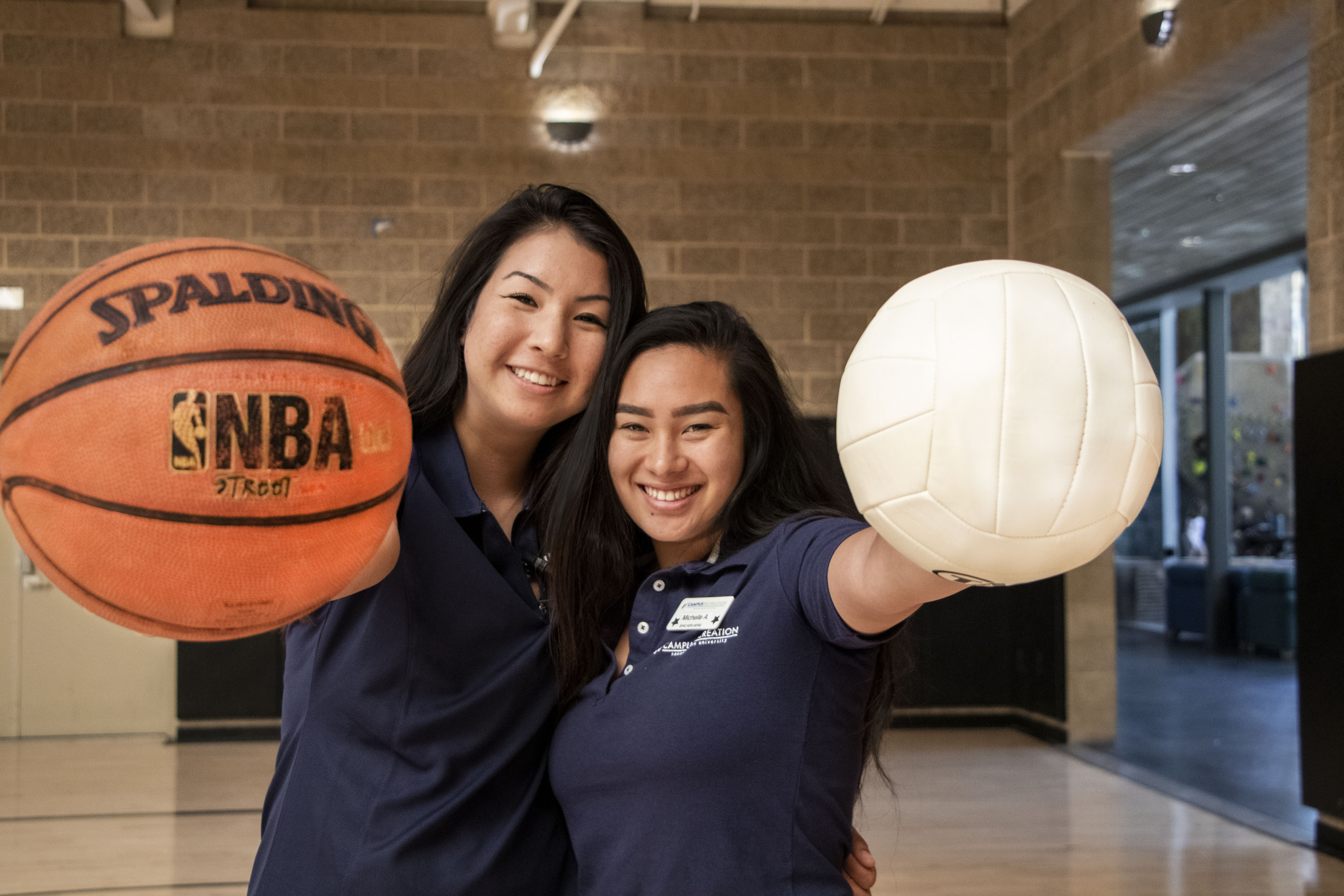 2 students holding a basketball and volleyball